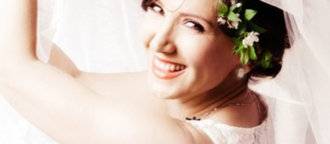 beautiful happy smiling bride play with her veil studio shot